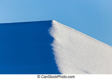 Snow on the roof of the house in winter