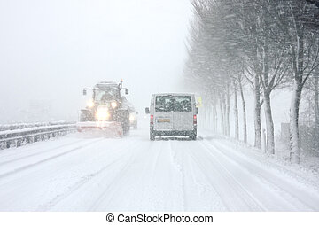 Snow plow cleaning the roads during a snowstorm in the...
