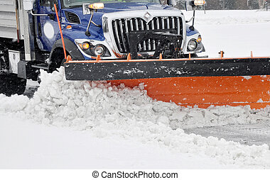 Snow plow clearing streets during a blizzard