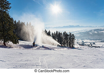 Snow production on a ski slope - Working snow cannons on a...