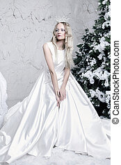 snow queen in white dress in ice room