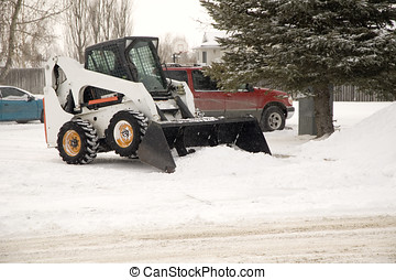 Snow removal - Bob cat removing snow in a parking lot.