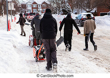 Snow removal team walking with shovels