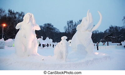 Snow sculptures of mammoths at winter evening on snow small...