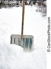 Snow shovel in snow drift after storm