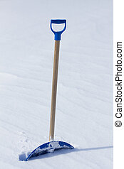Snow shovel standing in the snow