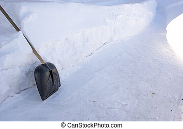 Snow shovel. Winter background. A snow shovel stands next to a pile of snow. To rake paths in winter.