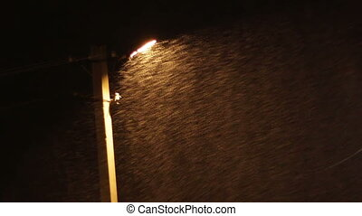 Snow Storm at Night on the Background of a Lamppost.