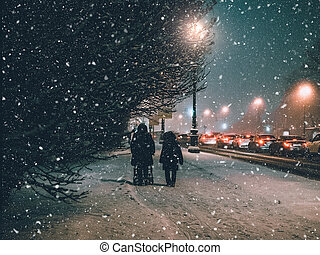 Snow storm in the night city of Europe. Silhouettes of people walking on a snowy street
