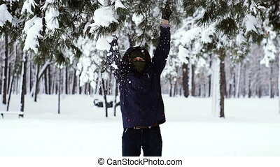 Snow. The guy is rubbing a snowy branch from which the snow falls