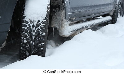 Snow tire. - Closeup of snowtire on SUV during snowstorm....