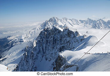 Snow white peaks in clouds and blue sky, Mont Blanc, France