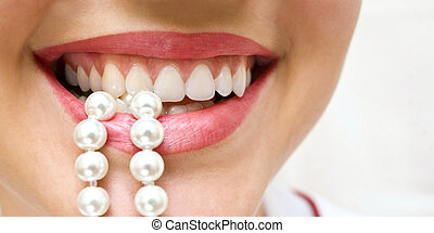 snow-white pearls of teeth - a woman smiles showing white...
