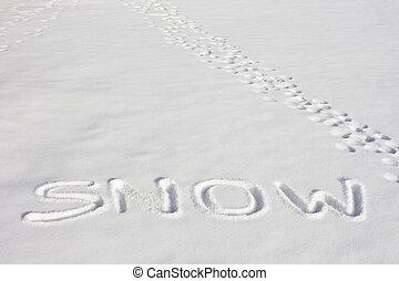 SNOW Written In A Snowy Field Beside Footprints
