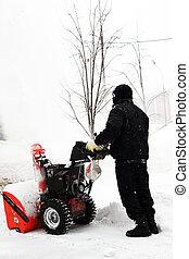 Snowblower in city under snowfall