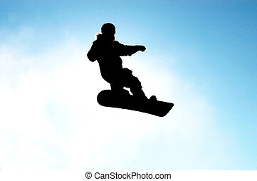 Snowboard - A snowboarder in action against blue sky...