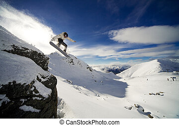 Snowboard cliff drop - Snowboarder riding off cliff with...