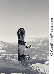 Snowboard in snow on off-piste slope at winter morning....
