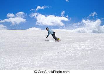 Snowboarder against blue sky