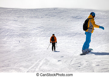 Snowboarder and skier downhill on off-piste - Snowboarder...