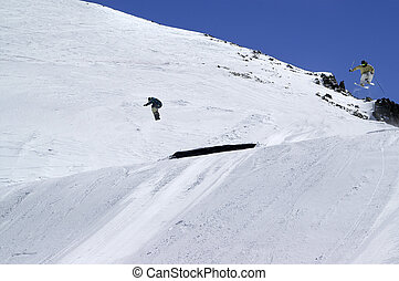 Snowboarder and skier jumping in snow park at ski resort on sunny winter day