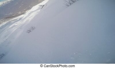 Snowboarder backcountry ride from top of snowy mountain. High speed. Extreme