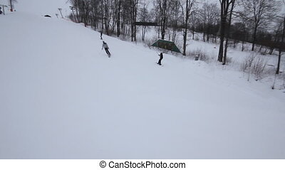 Snowboarder coming down on a snowbo
