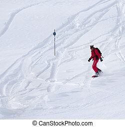 Snowboarder descends on snowy off-piste slope after snowfall...
