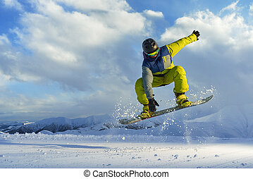 snowboarder does the jumping trick. snow scatters pieces of...