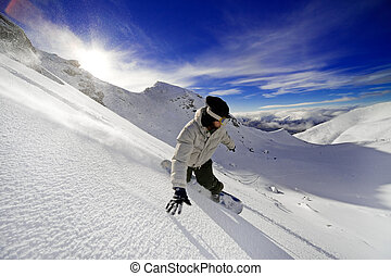 Snowboarder doing a toe side carve with deep blue sky in...