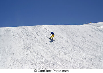 Snowboarder downhill in terrain park at ski resort
