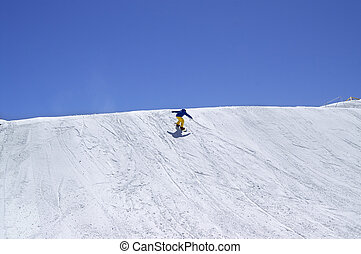 Snowboarder downhill in terrain park on ski resort at sun winter day