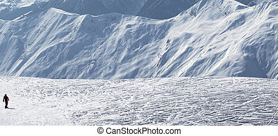 Snowboarder downhill on snow off-piste slope in sun winter...