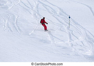 Snowboarder downhill on snowy off-piste slope after snowfall...
