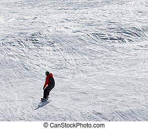 Snowboarder downhill on snowy off-piste slope in sun winter...