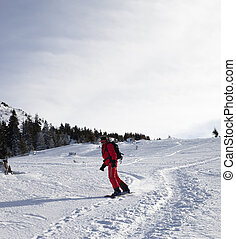 Snowboarder downhill on snowy off-piste slope in winter...