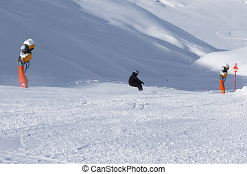 Snowboarder downhill on snowy ski slope with snow cannons at...