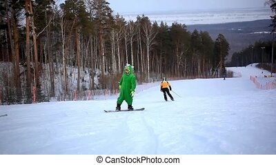 Snowboarder dressed kigurumi  on piste in high mountains and by passing skiers