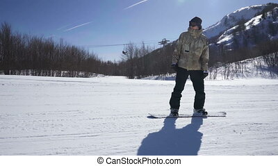 snowboarder enjoying a mountain ride at a ski resort on a sunny day