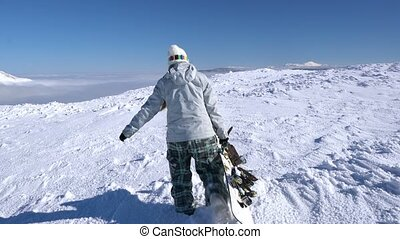 Snowboarder girl walking on snow at the upper point of the...