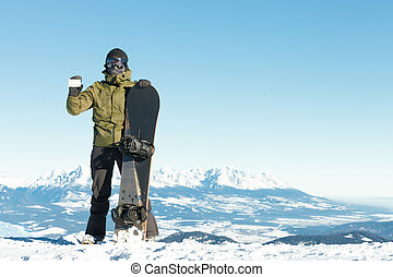 Snowboarder holding blank lift pass in one hand and snowboard in another with beautiful mountains on background