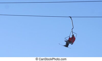 Snowboarder in a skilift - Snowboarder sitting in a skilift...