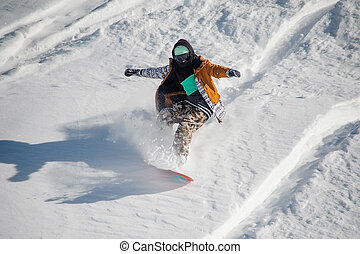 Snowboarder in colorful sportswear riding with snowboard down powder snow hill