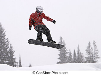 Snowboarder In Mid-Air - A snowboarder with a red coat...