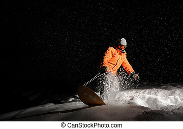 Snowboarder in orange sportswear and mask riding on a snowy hill at night