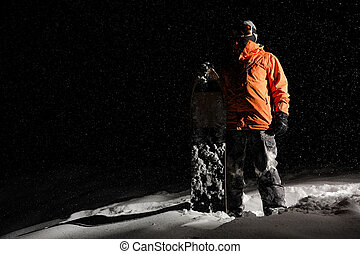 Snowboarder in orange sportswear and mask standing with a board on snowy hill at night