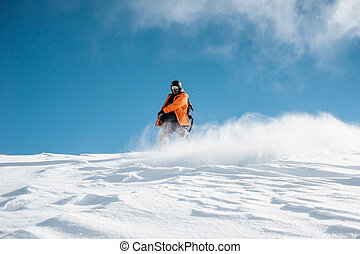 Snowboarder in orange sportswear riding down the powder snow hill