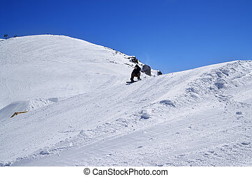 Snowboarder in snow park at ski resort on sunny winter day