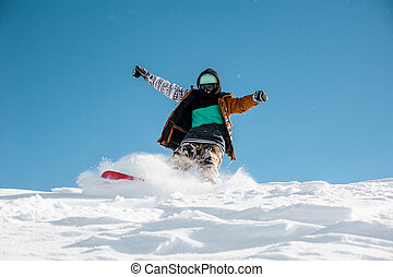 Snowboarder in stylish sportswear riding down the powder snow hill