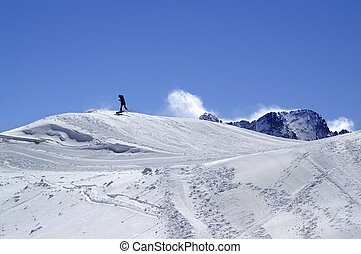 Snowboarder in terrain park at ski resort on sun winter day
